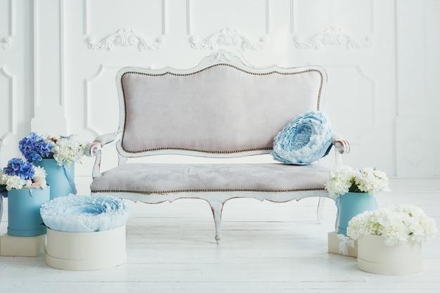 Интерьер с легким диваном в винтажном стиле и коробками с цветами вокруг