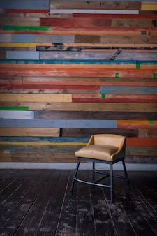 Interior with multi colored wooden wall dark wooden floor and vintage tiny chair