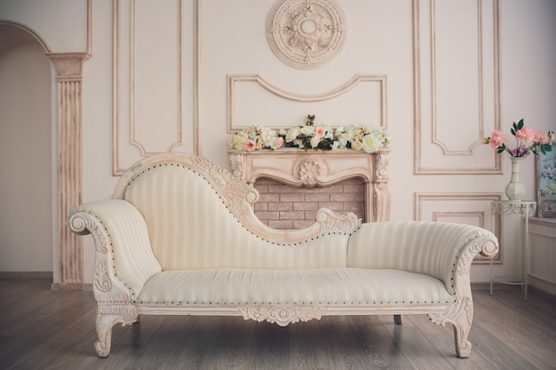 Interior with vintage furniture, light spring studio with beautiful white sofa and flowers in vases. white interior of studio with white and pink flowers for photo shooting.