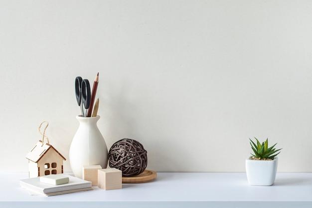 흰색 책상이나 선반, 빈 벽, 문구류, 장식용 식물이 있는 인테리어. 스칸디나비아 스타일.