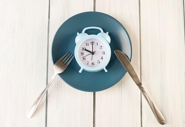Концепция прерывистого голодания. белый будильник на пустой голубой тарелке. вид сверху, копия пространства.