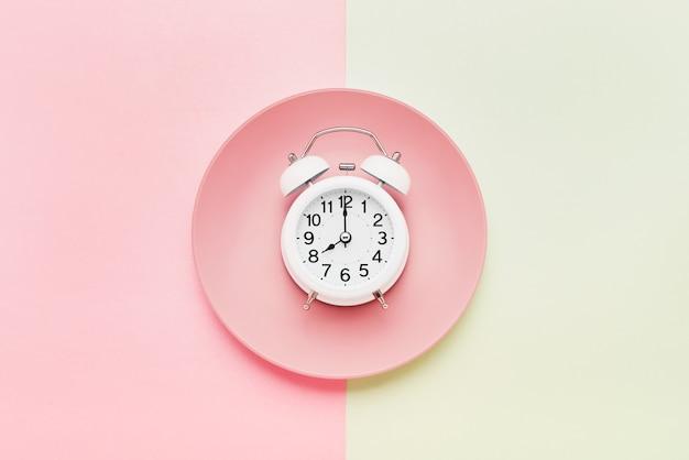 Концепция прерывистого голодания. белый будильник на пустой розовой тарелке на розово-зеленом фоне. вид сверху, скопируйте место для текста