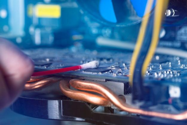 오래된 개인용 컴퓨터의 내부 부품. 먼지가 많은 마더보드와 비디오 카드. 마법사가 비디오 카드를 청소합니다. 고장난 pc.