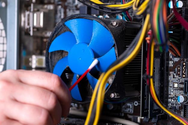오래된 개인용 컴퓨터의 내부 부품. 먼지가 많은 마더보드, 비디오 카드 및 팬. 마스터는 먼지로부터 pc 쿨러를 청소합니다. 고장난 pc.