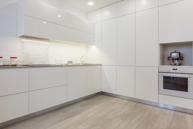 전경에 있는 현대식 주방의 내부 사진 수도꼭지와 주방 싱크대