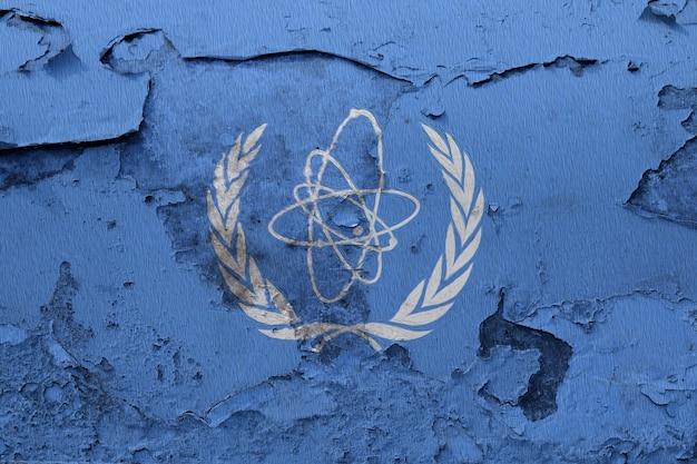 International atomic energy agency flag painted on grunge cracked wall