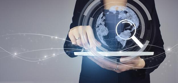 国際的なビジネスコンセプト。インターネットマップとナビゲーションの概念。デジタルホログラム惑星と灰色の背景に検索サインと実業家の手の白いタブレット。地図とイノベーションの概念