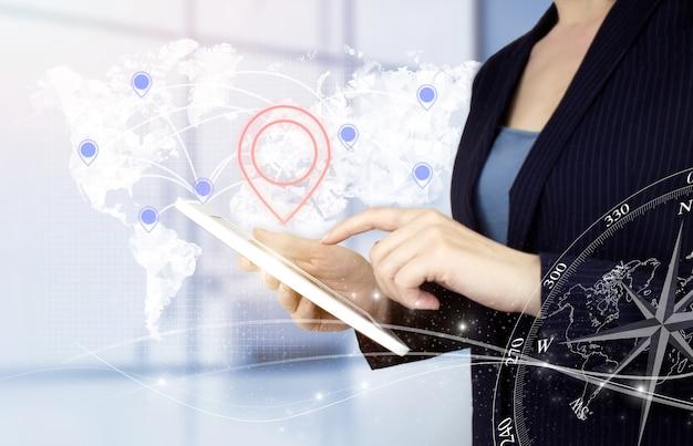 国際的なビジネスコンセプト。デジタルホログラムの世界、地球、地図、明るいぼやけた背景にロケーションマーカーサインを備えたハンドタッチの白いタブレット。 gpsマップ、モバイルアプリのpinアドレスの場所。