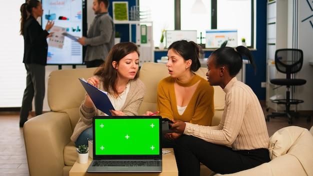 국제 비즈니스 팀은 카메라 앞에서 모형 노트북으로 회사 계획에 대해 논의하는 아프리카 여성과 이야기하고 있습니다. 리더는 크로마 키 디스플레이가 있는 그린 스크린 pc를 사용하여 프로젝트 전략을 설명합니다.
