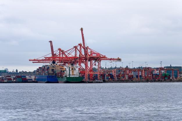 상업 항구에 컨테이너 화물 및 갠트리 크레인이 있는 국제 화물선