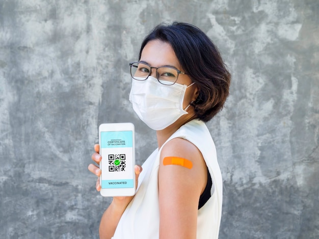 Международный сертификат вакцинации, умный цифровой паспорт с qr-кодом на экране смартфона. вакцинированная азиатская женщина с гипсовой повязкой, показывающая паспорт здоровья и свидетельство о вакцинации.