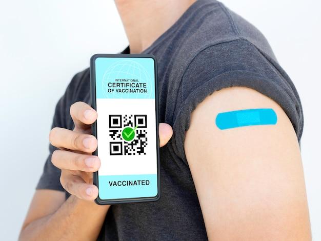 Международный сертификат вакцинации, умный цифровой паспорт с qr-кодом на экране смартфона. вакцинированный мужчина с синей повязкой и пластырем с паспортом здоровья и свидетельством о вакцинации.