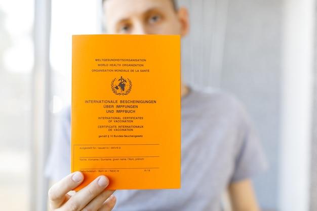 男性の手にドイツ語と英語のテキストを使用した予防接種の国際証明書。ワクチンの概念