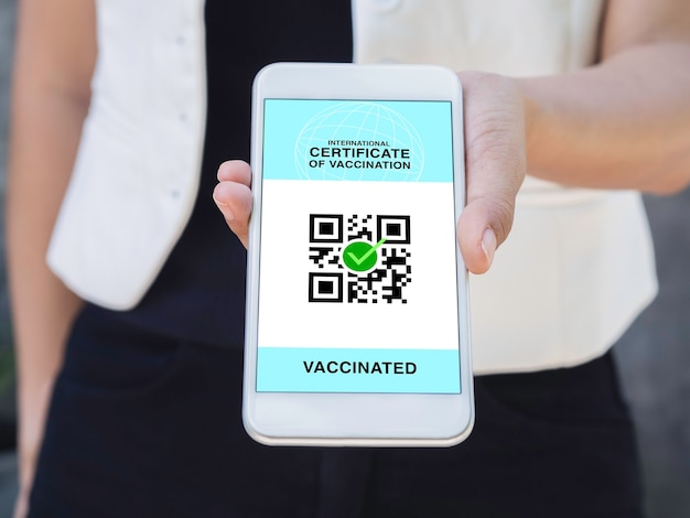 International certificate of vaccination, smart digital passport with qr code on smartphone screen. close up vaccinated woman hand showing health passport of vaccination certification.
