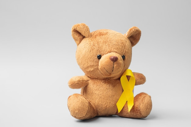 Международный месяц осведомленности о детском раке, детская игрушка с золотой лентой для поддержки жизни детей. концепция здравоохранения и всемирного дня рака