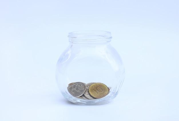 Международные монеты в стеклянной банке на белом фоне
