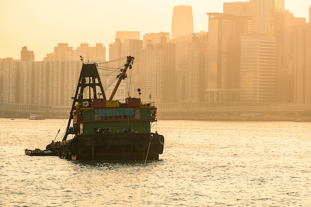 International container cargo ship in the ocean with hong kong cityscape