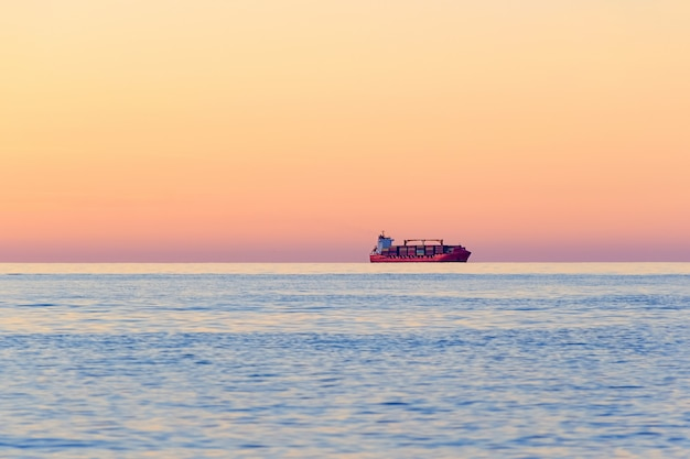 International container cargo ship on the open sea horizon at sunset. water transport international.