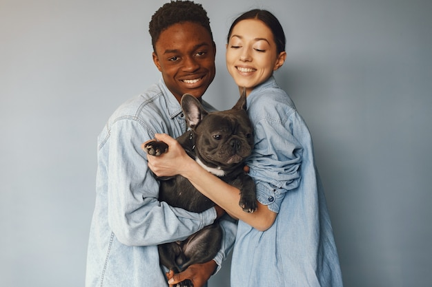 International couple on a blue background with a dog