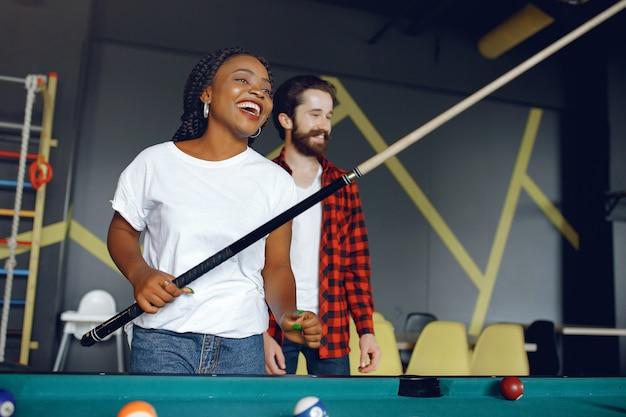 International couple playing a billiard in a club