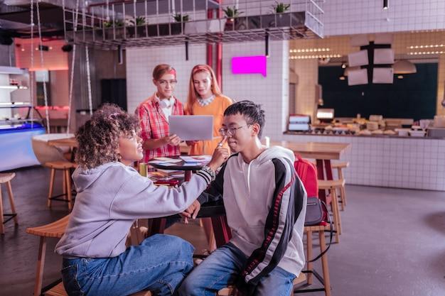 Интернациональная пара. силуэт довольных учеников, которые смотрят в ноутбук во время работы над своим проектом