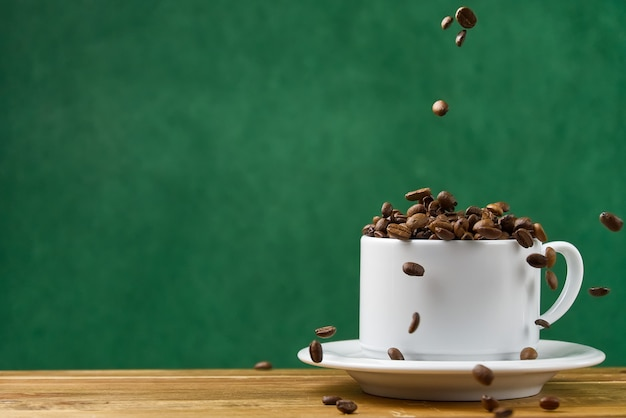 International day of coffee concept. close-up white coffee cup full of coffee beans. coffee beans fall into the white mug