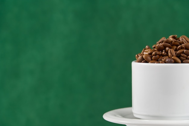 International day of coffee concept. close-up white coffee cup full of coffee beans on dark green background.