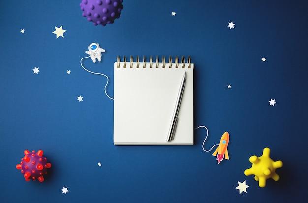 Международный день полета человека в космос. 12 апреля всемирный день космонавтики. спиральная тетрадь на абстрактной изолированной голубой стене. мультяшная галактическая концепция.
