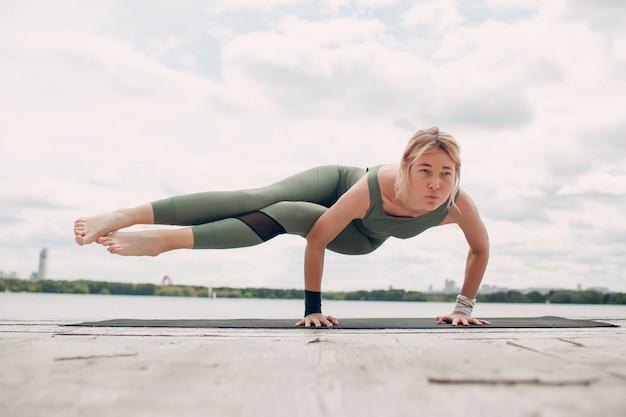 International day of yoga. young woman practicing hatha yoga at lake coast,