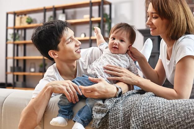 소파에 집에서 국제 가족, 포옹하고 인생을 즐기십시오. 행복한 가정 생활.
