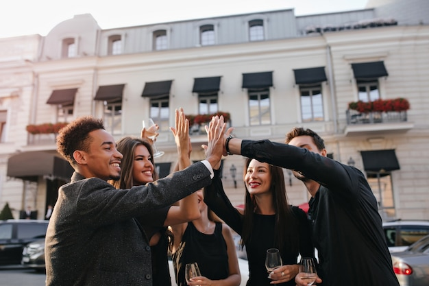 Amici internazionali schiaffeggiano le mani per strada