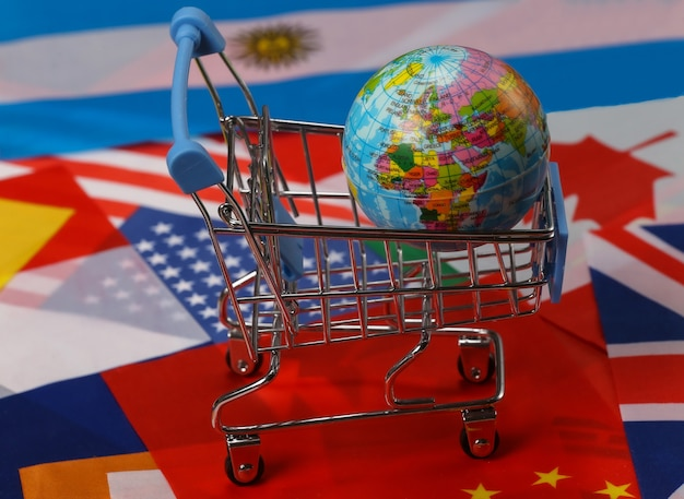 International, global shopping. supermarket trolley with globe on the background of many flags of the countries
