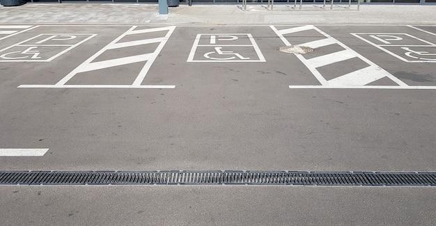 ショッピングセンターの駐車場にある国際的なハンディキャップのシンボル。スペースは、追加の白い斜めのストライプによって両側に明確に示されます。