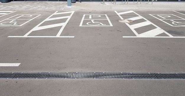 International handicap symbol in a parking lot of a shopping center. the space is clearly indicated on both sides by additional white diagonal stripes.