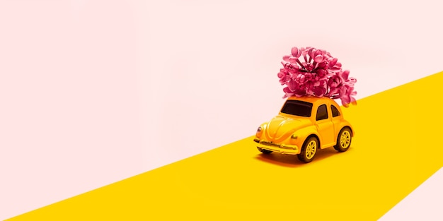 International happy women's day. toy yellow car with lilac flower branch on a pink background with place for text.