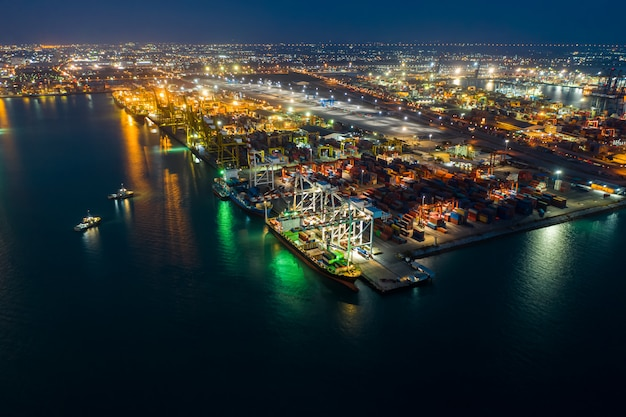 International import and export business by shipping containers marine and cargo station in thailand at night aerial view