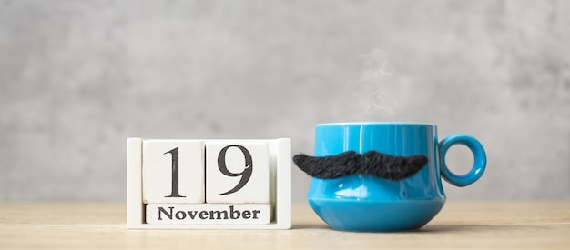 International men day with november 19 calendar, blue coffee cup or tea mug and black mustache decor on table. happy father day and celebration concept