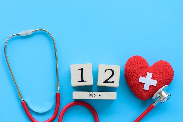 International nurses day, may 12. red heart with stethoscope on blue background.