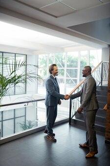 Международный партнер. афро-американский бизнесмен встречает своего международного партнера и пожимает ему руку