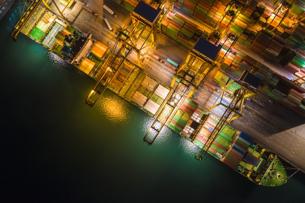 International sea freight station by large cargo containers ship above view frome drone camera at night