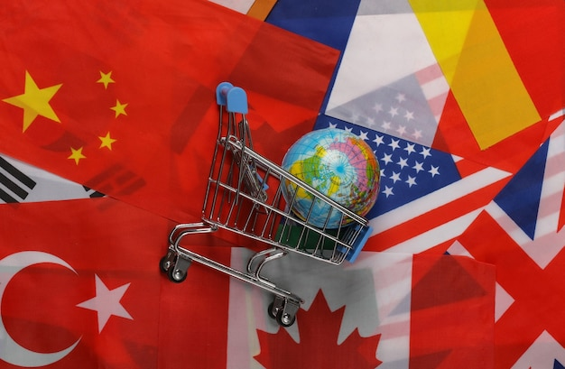 International shopping. supermarket trolley with globe on the background of many flags of the countries