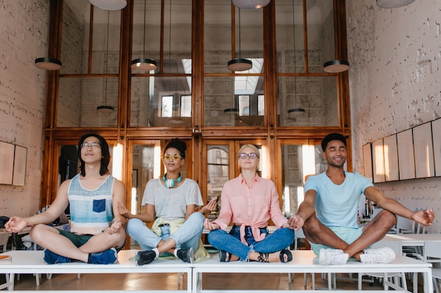 Studenti internazionali che meditano sui banchi in biblioteca, rilassandosi prima degli esami. amici universitari che fanno yoga sul tavolo con gli occhi chiusi.