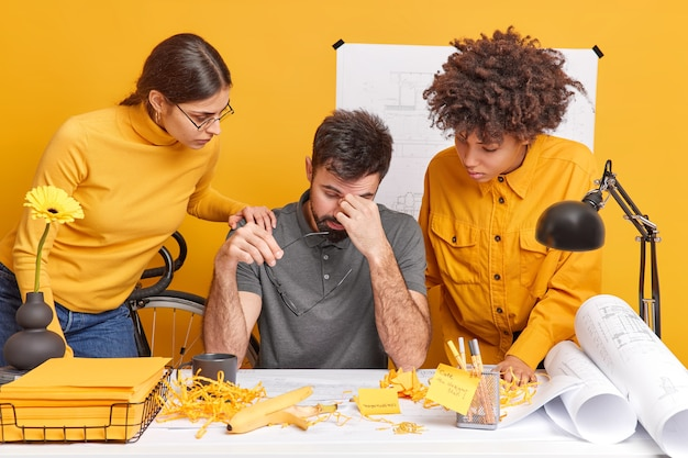 International students think about solution of problems with graphic drawings check blueprints of architectural project pose at desktop. tired male office worker takes off spectacles two helpers near