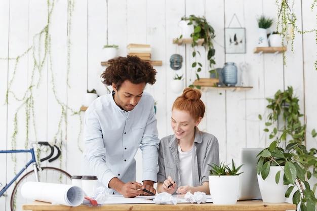 Team internazionale di due giovani designer ambiziosi che lavorano insieme su un progetto comune