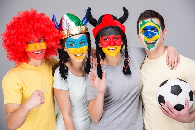 Международная команда с национальными флагами на лицах.