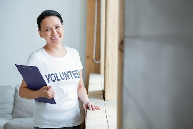 국제 자원 봉사. 카메라를 응시하고 웃는 동안 클립 보드를 들고 열정적 인 성공적인 여성 자원 봉사자