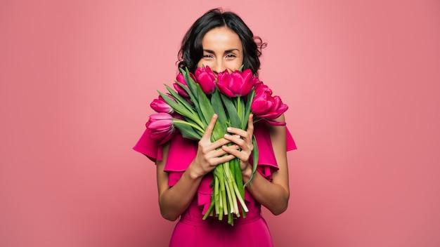 Международный женский день. чрезвычайно счастливая женщина в ярко-розовом платье нюхает букет весенних цветов, который она держит в руках.