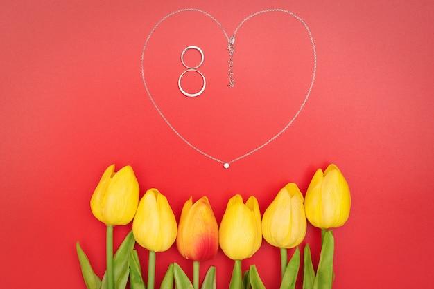 빨간색 배경에 꽃과 하트 모양 목걸이와 국제 여성의 날