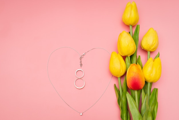 International women's day with flowers and heart shape necklace on pink background
