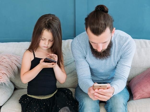Интернет зависимость. чрезмерное использование мобильных устройств. папа и ребенок сидят на диване и смотрят на свои телефоны. вторжение технологий в воспитание детей.
